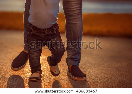 Learning to walk.Image of one year old baby boy having his first steps with the help of his mother.  - stock photo
