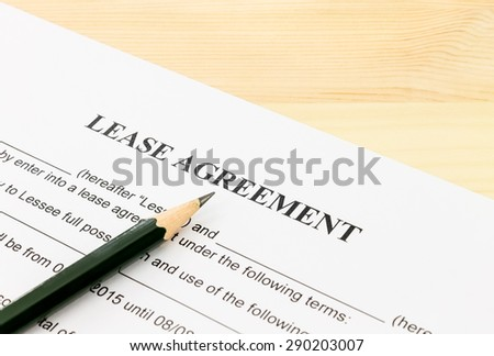 Lease Agreement Contract Document and Pencil Bottom Left Corner on Wood Table. Legal document for business event - stock photo