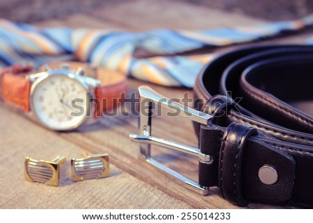 Leather belt, tie, cufflinks and watches on the old wood background. Toned image.  - stock photo