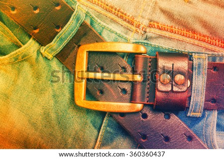 Leather belt with a gold buckle and aged jeans. Fashion, clothing and accessories. Bright art processing - stock photo