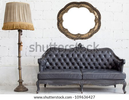 leather black antigue sofa in white room. - stock photo