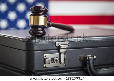 Leather Briefcase and Gavel Resting on Table with American Flag Behind. - stock photo