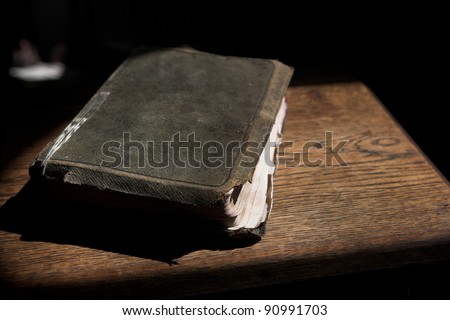 Leather covered old bible lying on a wooden table in a beam of sunlight Shallow Depth of field â?? Focus on Text â??Holy Bibleâ? - stock photo
