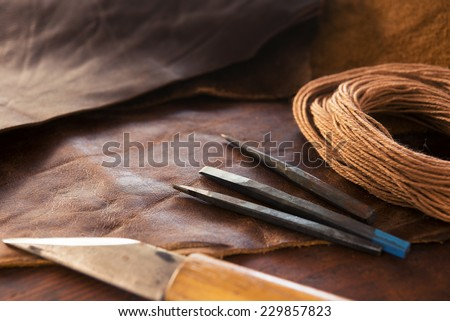 Leather craft. leather crafting tools and thread on a work table.  - stock photo