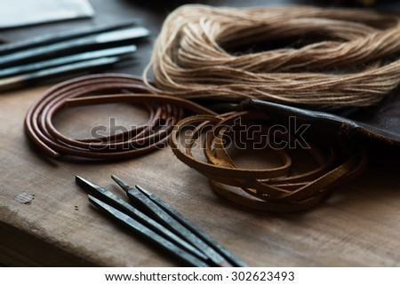 leather craft or leather goods making. work bench of a leather smith. Shallow depth of field. - stock photo