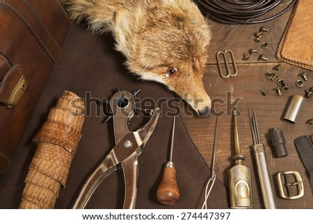 Leather craft tools and a stuffed fox - stock photo
