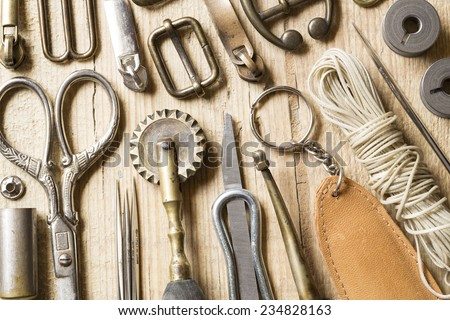 Leather craft tools,thread and buckles on a wooden background - stock photo