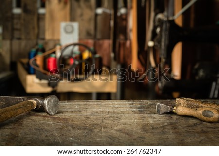 Leather crafting tools on working desk with the scratches. Blurred background of leather workshop. Copy space. - stock photo