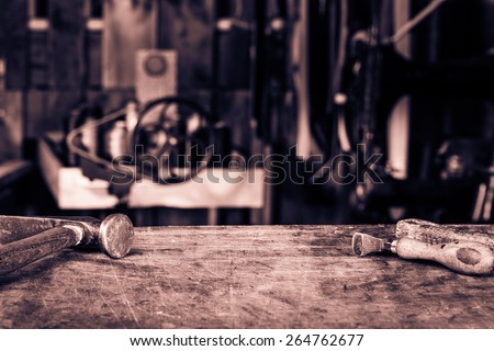 Leather crafting tools on working desk with the scratches. Blurred background of leather workshop. Copy space. Monochrome cream tone. Black and white photography. - stock photo