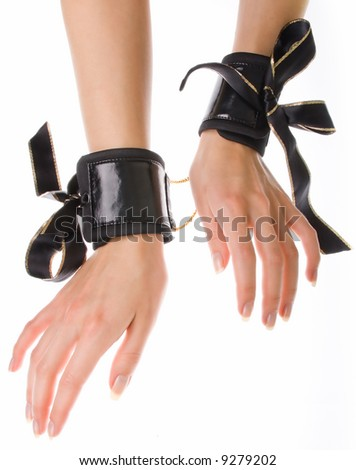 Leather handcuffs with golden chains on isolated background - stock photo