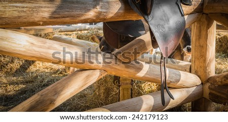 Leather horse saddle displayed on wooden fence  - stock photo