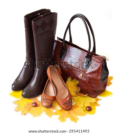 Leather luxury woman handbag, boots and shoes isolated on white background with autumn leaves. Autumn sales concept - stock photo