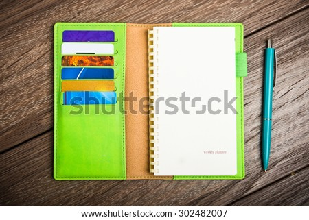 Leather organizer  with paper and pen on wood desk - stock photo