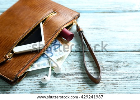 Leather purse with mobile phone and euro banknotes on wooden background - stock photo