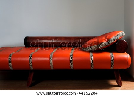 Leather red sofa on a background of a wall - stock photo