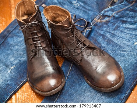 Leather shoes brown and blue jeans. Fashionable leather high boots. - stock photo