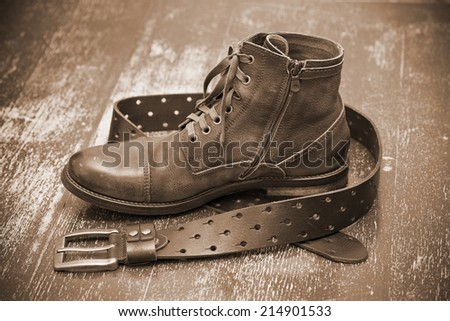 Leather shoes, leather belt. Autumn and spring shoes. Cowboy style. Vintage style. Photo toning in sepia - stock photo