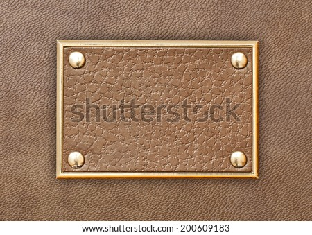 Leather tag in a metal frame on a background of brown leather - stock photo