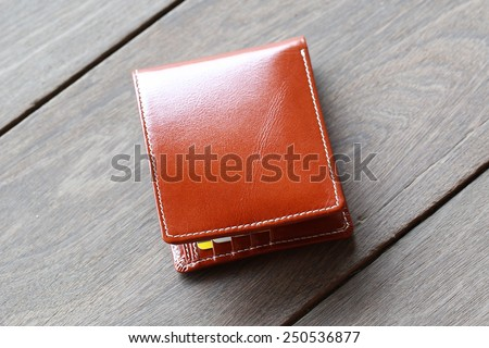 leather wallet brown leather on a wood background - stock photo