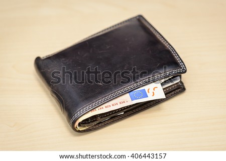 leather wallet with 50 Euro banknote inside on wooden table - stock photo