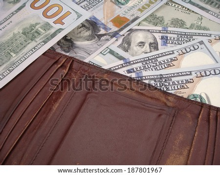 Leather Wallets Resting Upon Many United States One Hundred Dollar Notes. - stock photo