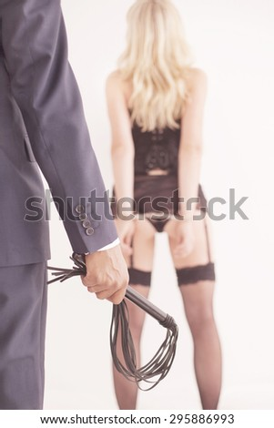 Leather whip held by dominant master in a suit - stock photo