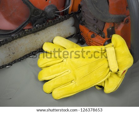 leather work gloves with chainsaw and helmet - stock photo