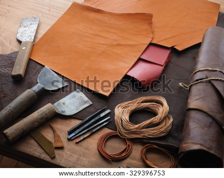 Leathersmith's work desk . Pieces of hide and leather working tools on a work table. - stock photo