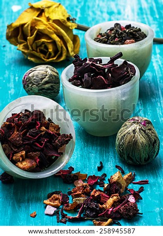 leaves of the tea brewing on turquoise wooden background - stock photo