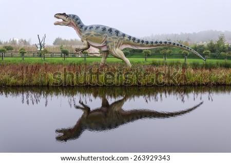 LEBA, POLAND- OCTOBER 01: Dinosaur model in with water reflection in open park in October 01, 2011, in Leba - Poland. Leba Park is 20ha area park in North Poland with original dinosaur models. - stock photo