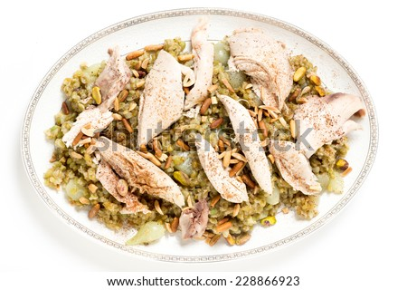 Lebanese cinnamon dusted chicken served on a bed of freekeh fire-dried green wheat with a garnish of toasted nuts, seen from above. - stock photo