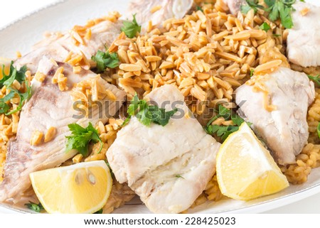 Lebanese-style fried fish served with caramelised onion flavoured rice and roasted almond slivers. - stock photo