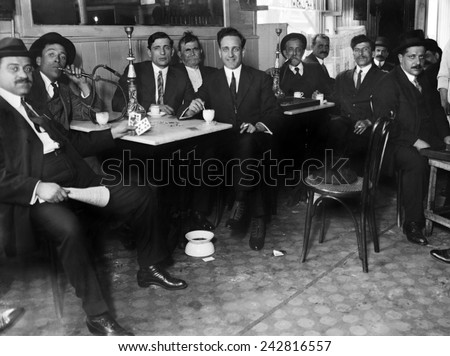 Lebanese-Syrian immigrant men in suits smoking hookahs in a restaurant in the New York City neighborhood, possibly Bay Ridge, Brooklyn. Ca. 1910. - stock photo