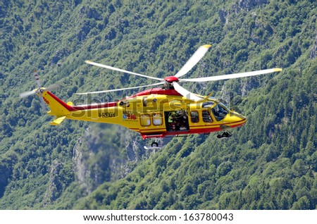 """LECCO, ITALY-MAY 28, 2011: An helicopter of Italian red cross in actionn during a rescue operation """" Grignetta """" mountain tin the Italian alps. - stock photo"""