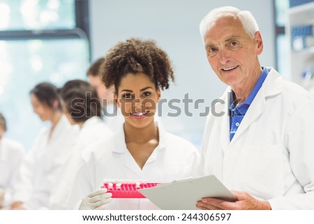 Lecturer and student smiling at camera in the lab at the university - stock photo