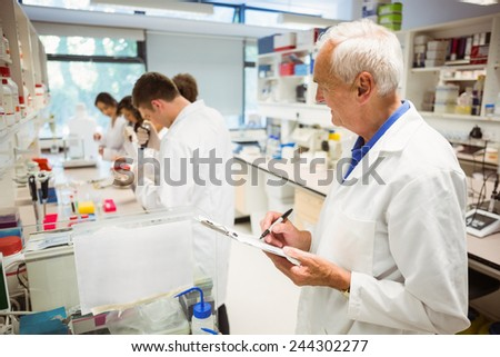 Lecturer watching over his science class at the university - stock photo