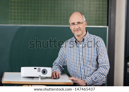 Lecturer with a slide projector sitting at a lectern in front of a blackboard as he prepares to start his lecture and presentation - stock photo