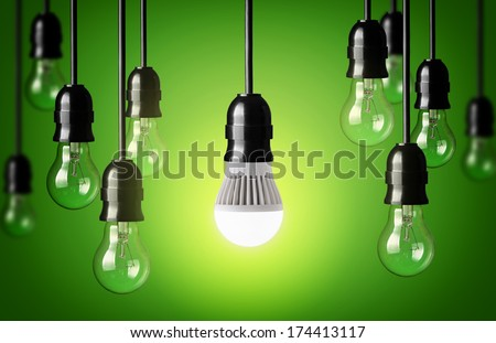 LED bulb and simple light bulbs.Green background - stock photo