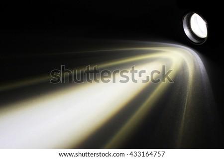 LED flashlight with a light beam at night. - stock photo