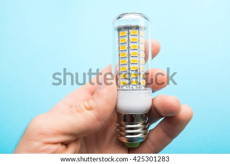 led lamp in hand on blue background