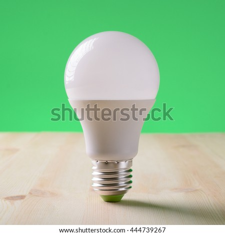 LED lamp standing on a wooden table on a green background - stock photo