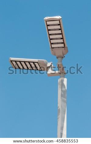 LED street lamp post on blue sky background - stock photo
