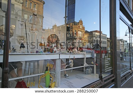 LEEDS, UK - JUNE 6, 2015: Reflections in shop window. The Leeds City Region is the UK's largest economy and population centre outside London, generating 4% of national economic output - stock photo