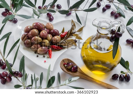 Left a white heart shape plate of green olives garnished with a bay leaf sprig, red peppers, an olive oil bottle on the right, spoon framed by olive tree branches on white background. Olives and oil. - stock photo