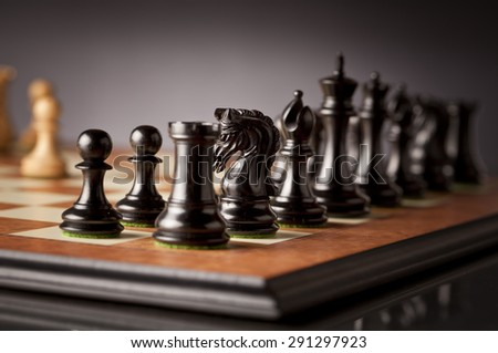 Left flank of the black army of luxurious chess pieces in focus on a wooden chessboard with dark background - stock photo