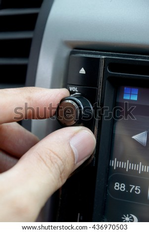 Left hand adjusting a volume control knob of the car's audio system. - stock photo