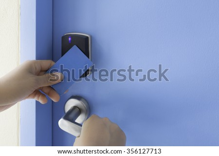 left hand hold key card touch on black electronic pad lock access control with right hand turn stainless steel door handle on blue door - stock photo