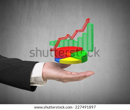 left hand holding 3d infographics overlapped on gray background, including colorful pie chart, green bar chart, red trend line - stock photo