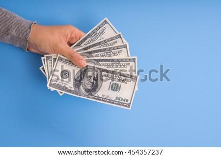 Left hand holding money, blue background. - stock photo