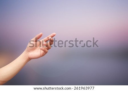 Left hand open palm gesture on blurred dusk sky night background:people with faithful reaching bless form heaven concept:man with hope of religion concept:believe of life and spiritual conceptual idea - stock photo